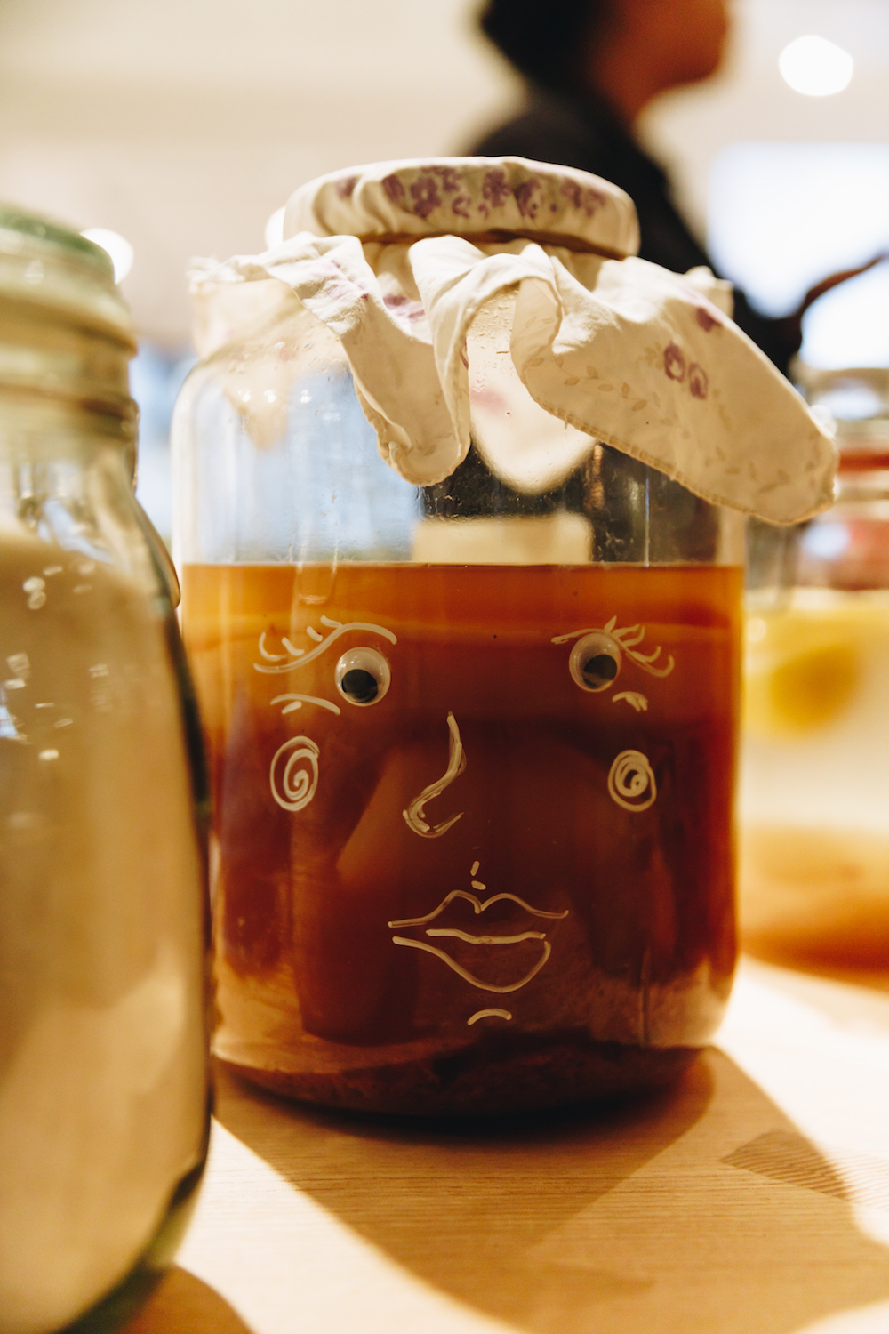 kombucha in glas vat with illustrated face